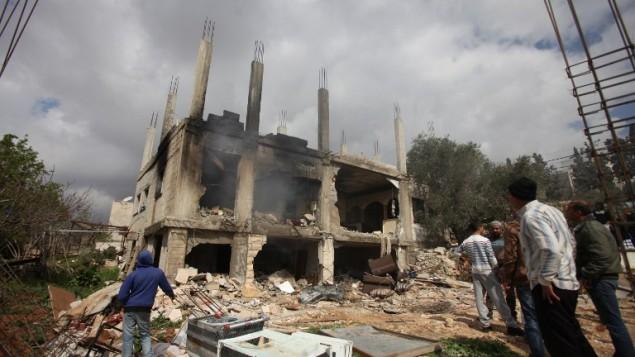 فلسطينيون يقفون امام بيت معتز وشاحة الذي قتل في هجوم للجيش الاسرائيلي على بيته في بير زيت 27 فبراير 2014 (أ ف ب)
