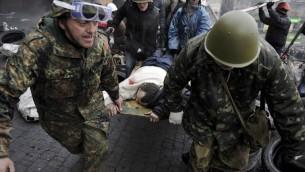 متظاهرون يحملون متظاهر جريح بعد اصتضام مع الشرطة في ساحة الاستقلال 20.02.2014 (أ ف ب)