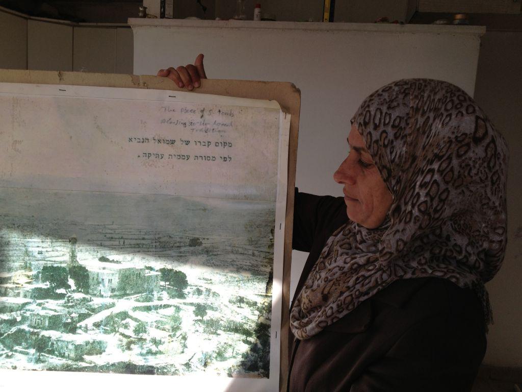 نوال بركات تعرض صورة التقطتت من الجو في فترة ماقبل 1971 عندما هدم الجيش الاسرائيلي 30 بيت / 31 ينلير 2014 (بعدسة الحانان ميلر/ طاقم تايمز أوف اسرائيل)
