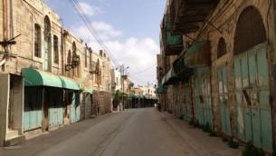 شارع الشهداء كان في الماضي سوقا حافلا اما اليوم فهو مغلق بوجوه المشاه الفلسطينين مما يجهله مهجورا معظم النهار (بعدسة الحانان ميلر / طاقم تايمز اوف اسرائيل)