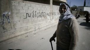 """احد سكان شرقي القدس امام جرافيتي """"العمل العربي= اختلاط"""" 10 فبراير 2014 (فلاش 90)"""