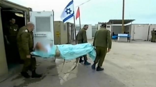 جنود اسرائيليين يرافقون مصاب سوري الى المشفى العسكري السري في هضبة الجولان (صورة من شاشة القناة الثانية الاسرائيلية)