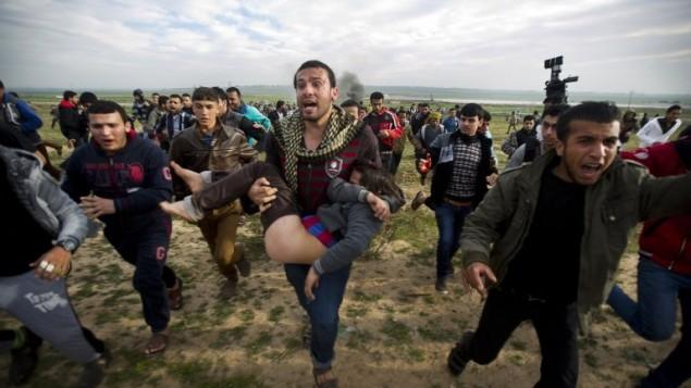 متظاهرون فلسطينيون في قطاع غزة يحملون صبي مصاب خلال اشتباكات مع قوات الجيش الاسرائيلي 21.02.2014 (أ ف ب )