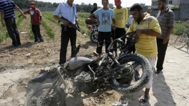 فلسطينيون حول دراجة نارية اصيبت بنيران اسرائيلية في دير البلح في غزة 2012 (عبد الرحيم خطيب / فلاش 90)