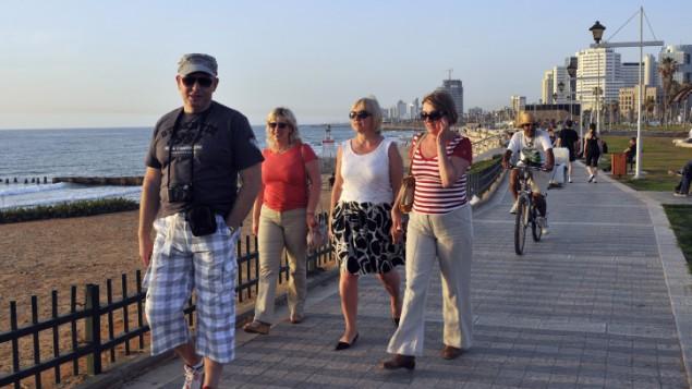 سائحون يتجولون على شاطئ تل أبيب (فلاش 90)