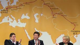 الرئيس الصيني تشي جنيبينج يجلس بين نائب الامين العام الالماني سيجمال جابريئيل (يسار) وهلينور كرافت امام خارطة القطار 29 مارس 2014 (AFP PHOTO / DPA/FEDERICO GAMBARINI GERMANY OUT)