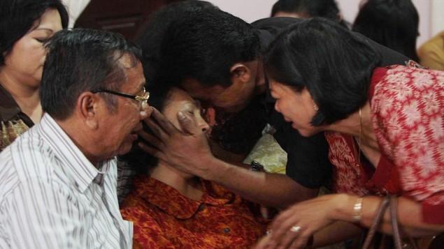اقرباء يحاولون مواساة ارلينا بنجايتان وريسمان سريجار، ، والدا رجل الاطفاء ابن ٢٤ تشاندرا سيريجار (أ ف ب)