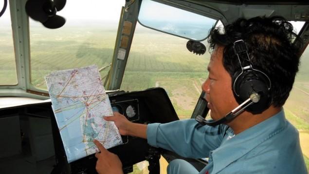 رجل من طاقم مروحية فيتنامية ينظر الى خارطة أثناء محاولات البحث والانقاذ للطائرة المفقودة 13 مارس 2014 (بعدسة باو مينه/ أ ف ب)