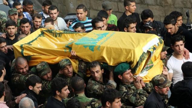 محاربو حزب الله اللبناني الشيعي يحملون جثمان زميلهم محمد علي عساف الذي لقي مصرعه في سوريا 24 فبراير 2014 (أ ف ب)