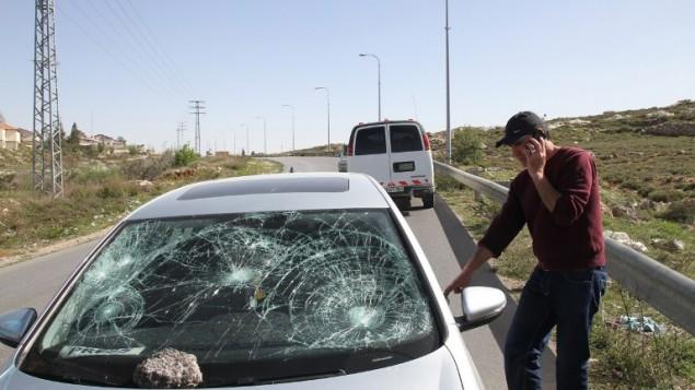 مصور وصحفي فرانس برس عباس مومني بجانب سيارته وآثار الضرر عليها جراء هجوم مستوطنين 7 مارس 2014 (أ ف ب/ اس تي أر)
