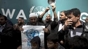فلسطينيون خلال مظاهرة ضد قرار اونروا بتقليص المساعدات الغذائية امام مقر اونروا في غزة 16 مارس 2014 (بعدسة محمد عبد/ أ ف ب)