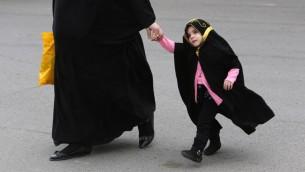 امرأة محجبة مع طفلة مغطاة من رأسها الى أخمص قدميها, مؤيدو القانون يزعمون بانه سوف يشرع العادات التي تمارس يوميا ( بعدسة أحمد الرباعي/ أ ف ب)
