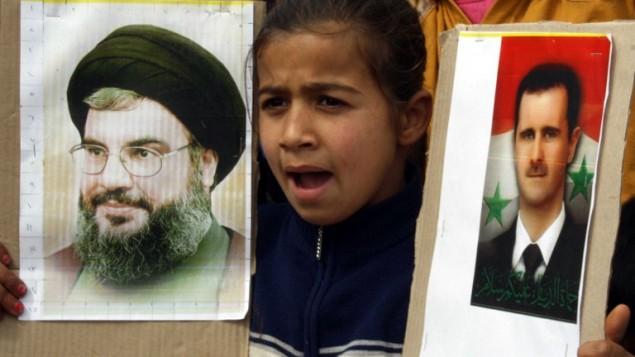 فتاة لبنانية تحمل صور لبشار الاسد وحسن نصرالله في مرجعيون لبنان ١٨ مارس ٢٠١٤ (بعدسة علي ضياء أ ف ب)