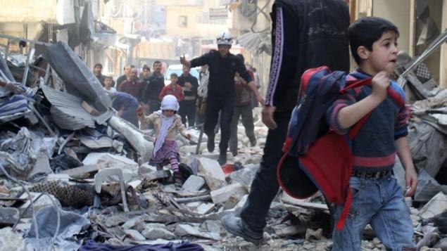 قوات الانقاذ تساعد عائلة سورية في حلب بعد سقوط صاروخ موجه اتجاه قوات موالية للنظام ٢٣ مارس ٢٠١٤ (بعدسة براء الحلبي/ أ ف ب)