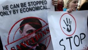 متظاهرون معارضون للتدخل الروسي بالقرم يحملون صورة بوتين مشبه بهتلر النازي في القرم 11 مارس 2014 (أ ف ب )
