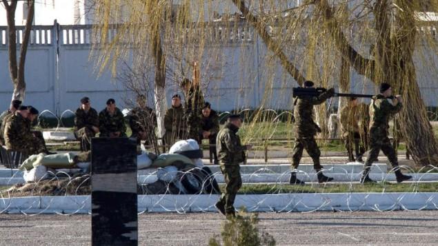 قوات جيش اوكرانية تنقل الاسلحة والمعدات الى السيارات في القرم ٢٣ مارس ٢٠١٤ (بعدسة ديميتري سيريبرياكوف/ أ ف ب)