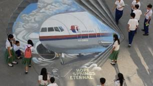 مانيلا، طلاب يقفون حول لوحة فنية رسمت تضامنا مع عائلات ضحايا الطائرة المفقودة، في مقاطعة مالاكي ١٨ مارس ٢٠١٤ (بعدسة تد الجيبي/ أ ف ب)