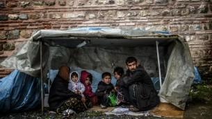 عائلة سورية من حلب تختبئ من المطر في اسطنبول ٨ مارس ٢٠١٤ (بعدسة بولينت كيلينك / أ ف ب)