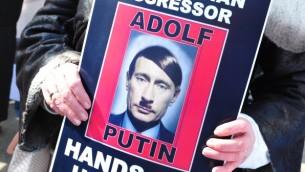 مظاهرات في واشمطن ضد العداء الروسي، صورة تشبه بوتين بهتلر ٦ مارس ٢٠١٤ (أف ب)