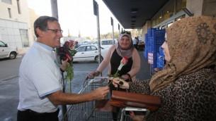 يتسحاق جليك يعرض الزهور على متشرّية فلسطينية في سوبرماركت رامي ليفي في الون شفوت ١٤ نوفمبر ٢٠١٤ (بعدسة يوسي زمير)