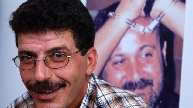 قدورة فارس، وزير فلسطيني سابق والرئيس الحالي لنادي السجناء الفلسطينيين امام صورة لمروان برغوثي (فلاش 90)