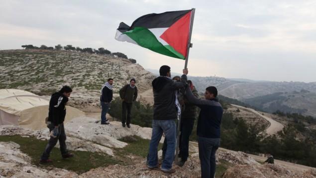 نشطاء فلسطينيون ينصبون العلم الفلسطيني في منطقة إي ١ شرقي القدس والتي هي جزء من منطقة سي (بعدسة عصام ريماوي/ فلاش ٩٠)