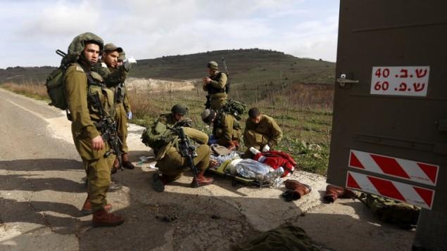 جنود في الجيش الاسرائيلي يستعدون لاخلاء زميلهم الذي اصيب في الانفجار عند الحدود السورية بجانب قرية مجدل شمس 18 مارس 2014 (بعدسة جلاء معاري / أ ف ب)