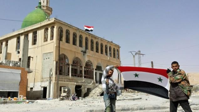 محاربون مؤيدون للنظام يحملون العلم السوري في قرية السهل بجانب يبرود 4 مارس 2014 (أ ف ب/ اس تي أر)