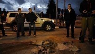 مدنيون ورجال امن اسرائيليين يقفون بجانب حفرة نتجت عن صقوط صاروخ في الصحراء الجنوبية (أ ف ب)