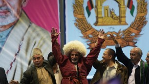 مرشح الرئلسة الافغاني أشرف غاني احمدازي يرتدي قبعة تقليدية قدمة له كهدية خلال احتفال نهاية سباق الانتخابات 2 ابريل 2014  AFP PHOTO/WAKIL KOHSAR