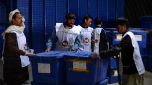 عمال لجنة الانتخابات الافغانية ينقلون صناديق الاقتراع 3 ابريل 2014 (شاه ماري/ ا ف ب)