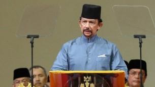 سلطان بروناي حسن بلقيه يلقي خطابا خلال حفل رسمي لتنفيذ قانون الشريعة في بندر سيري بيغاوان في 30 أبريل 2014 (AFP).