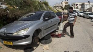 """رجل فلسطيني في بيت حنينا يغير إطارات سيارته 24 مارس 2014 بعد أن ثقب من يشتبه بانهم مخربين يهود  إطارات عشرات السيارات الفلسطينية في أحدث ما يسمى """"تدفيع الثمن"""" والتي هي جرائم الكراهية ة ( أ ف ب / أحمد الغرابلي)"""