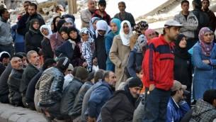 """صورة مقدمة من وكالة الانباء السورية الرسمية (سانا) لسوريين في انتظار توزيع المساعدات الغذائية 31 مارس 2014  """"AFP PHOTO / HO / SANA"""""""