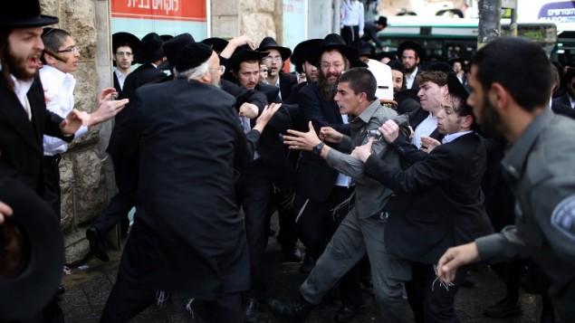 مشاجرات مع الشرطة الاسرائيلية خلال تظاهرة ضد الخدمة العسكرية الإلزامية في القدس يوم 10 أبريل 2014. حيث تجمع المئات من المتظاهرين في حي المتدينين ميا شيعاريم وتم توقف حركة المرور وألقوا الحجارة والزجاجات على الشرطة كما أن خمسة منهم اعتقلوا. وجاءت المظاهرة بعد شهر ووافق النواب الإسرائيلية من خلال القانون الذي سوف يجبر اليهود المتطرفين إما يخدمون في الجيش أو أداء الخدمة المدنية. AFP PHOTO / مناحيم كاهانا