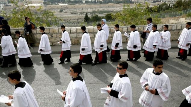 رجال الدين الكاثوليك يشاركون في موكب أحد الشعانين التقليدية . حاملون الزيتون إلى مدينة القدس القديمة في 13 أبريل عام 2014. الاحتفال هو علامة بارزة في التقويم المسيحي، بمناسبة العودة المظفرة المسيح إلى القدس الأسبوع قبل وفاته، عندما استقبله حشد هتاف يلوحون سعف النخيل. أحد الشعانين يصادف بداية الأسبوع الأكثر الرسمي في التقويم المسيحي. AFP PHOTO
