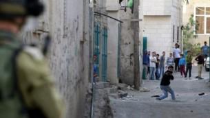 متظاهر فلسطيني يرمي الحجارة بواسطة مقلاع على قوات الجيش الاسرائيلي خلال اشتباكات في مخيم عايدة 14 ابريل 2014 (Musa al-Shaer/AFP)