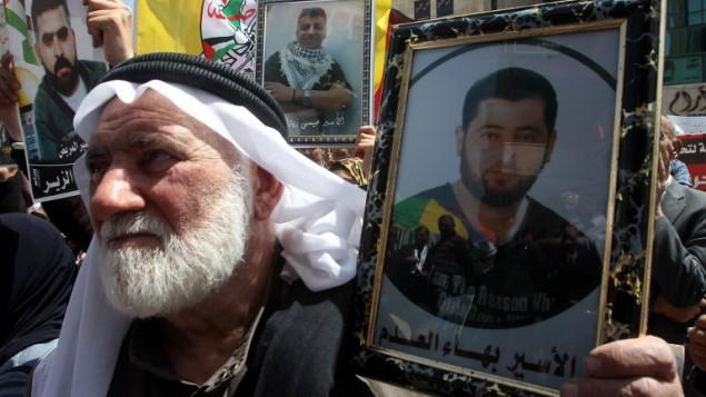 مسن فلسطيني يحمل صورة قريبه الاسير في مظاهرة بذكرى يوم الاسير في الخليل ١٧ ابريل ٢٠١٤ (حازم بدر / أ ف ب)