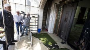"""الشيخ رائد صلاح  (L)، زعيم الجناح العربي اسرائيلي للحركة الإسلامية الراديكالية، يتفقد مدخل مسجد في المدينة  أم الفحام  18 أبريل 2014 بعد أن ترك المخربين الكتابة المعادية للعرب على جدران المسجد بين عشية وضحاها وحرقوا باب المبنى. الحادث هو الاحدث في سلسلة من الهجمات العنصرية والدينية """"دفع الثمن"""" على مدى الأسابيع القليلة الماضية. رسمت عبارة """"العرب خارج"""" باللغة العبرية. AFP PHOTO"""