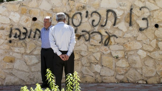 """أم الفحام  18 أبريل 2014 بعد أن ترك المخربين الكتابة المعادية للعرب على جدران المسجد بين عشية وضحاها وحرقوا باب المبنى. الحادث هو الاحدث في سلسلة من الهجمات العنصرية والدينية """"دفع الثمن"""" على مدى الأسابيع القليلة الماضية. رسمت عبارة """"العرب خارج"""" باللغة العبرية. AFP PHOTO"""