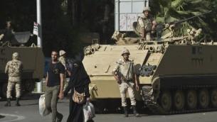 زوج مصري  يمشي امام دبابة تابعة للجيش كما تقف قوات الأمن حراسة خارج جامعة القاهرة في العاصمة القاهرة يوم 23 أبريل 2014. AFP PHOTO / خالد دسوقي