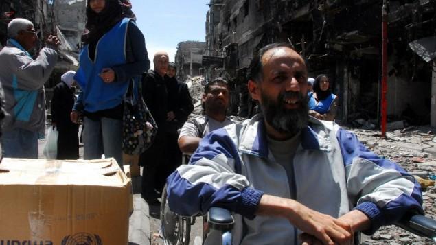 صورة صادرة عن وكالة الانباء السورية الرسمية (سانا) يوم 24 أبريل 2014، لسوريين  ينتظرون صناديق من المساعدات الغذائية التي يتم توزيعها من قبل وكالة إغاثة الأمم المتحدة (الأونروا) في مخيم للاجئين الفلسطينيين اليرموك جنوب سوريا . AFP PHOTO / HO / SANA