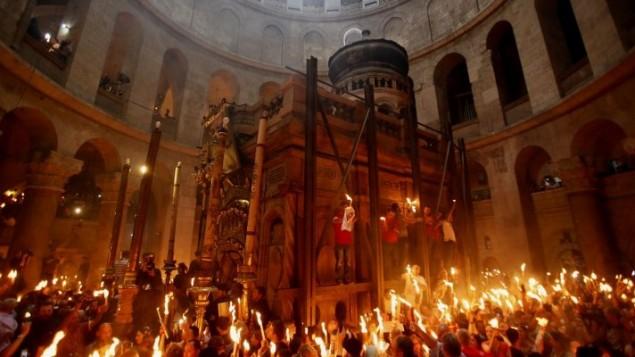 """المصلين المسيحيين الارثوذكس اثناء صمد الشموع المضاءة من """"النار المقدسة"""" حيث تجمع الآلاف في كنيسة القيامة في مدينة القدس القديمة  19 أبريل 2014 (تصوير: غالي تيبون / أ ف ب)"""