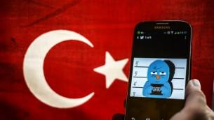 صورة توضيحية لعصفور التويتر تحت الاعتقال على شاشة هاتف ذكي خلفه العلم التركي 26 مارس 2014 (اوزان كوزي/ أ ف ب)