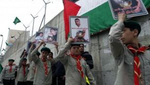 شباب فلسطيني يرفع لافتات خلال مسيرة تضامن من أجل الأسرى الفلسطينيين في السجون الإسرائيلية، التي نظمتها حماس في مخيم شعفاط للاجئين في القدس على 19 أبريل 2013 (Flash90).
