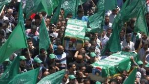 فلسطينيون يرفعون  الراية الخضراء لحركة المقاومة الاسلامية حماس  اثناء جنازة اثنين من أعضاء حماس، عادل وعماد عوض الله، اللذان قتلا بأيدي القوات الإسرائيلية في عام 1998، بعد أن أعادت إسرائيل رفات المقاتلين الفلسطينيين إلى أسرهم لدفنها، في 30 نيسان 2014 (Esam Rimawi/ flash 90)