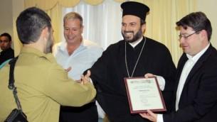 جندي عربي مسيحي يحصل على شهادة تقدير من الأب جبرائيل نداف في الناصرة (مقدمة  من مكتب المتحدث باسم الجيش الإسرائيلي)