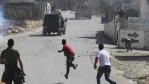 صورة توضيحية فلسطينيون يرمون الحجارة على سيارة الجيش الاسرائيلي (عصام ريماوي/ فلاش ٩٠)