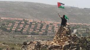 رجل فلسطيني يلوح في علم فلسطين بجانب مستوطنة عوفرا (فلاش 90)
