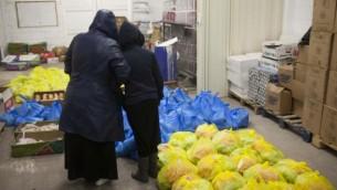 امرأة تقف وابنتها في مركز لتوزيع الغذاء للمحتاجين في القدس 2013 (فلاش 90)